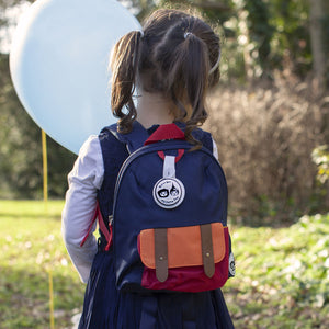 Zip and Zoe by Babymel mini backpack & safety harness-reins navy colourblock, girl wearing backpack with balloon in park | toddler backpack with reins | toddler rucksack | boys backpack | backpacks for girls | kids school bags | kids backpacks
