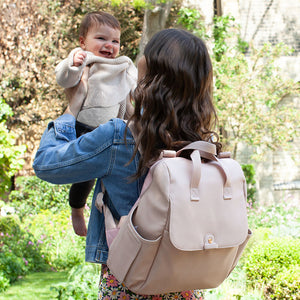 Babymel convertible changing bag, Robyn vegan leather blush, mum wearing backpack and holding baby, faux leather PU backpack changing bag, rucksack