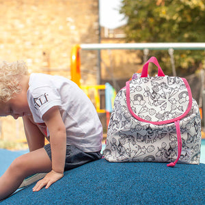 Zip and Zoe by Babymel colour & wash backpack, unicorn, girl sitting next to backpack in playground | unicorn backpack | school bags for girls | kids backpacks | kids colouring