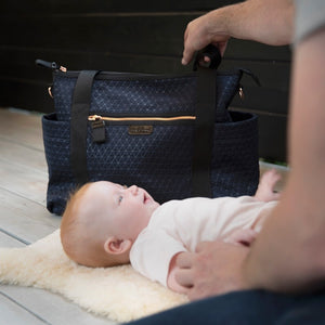 Babymel changing bag Cara ultra-lite navy scuba emboss, baby on mat with bag in the background, neoprene changing bag, handbag, shoulder bag.
