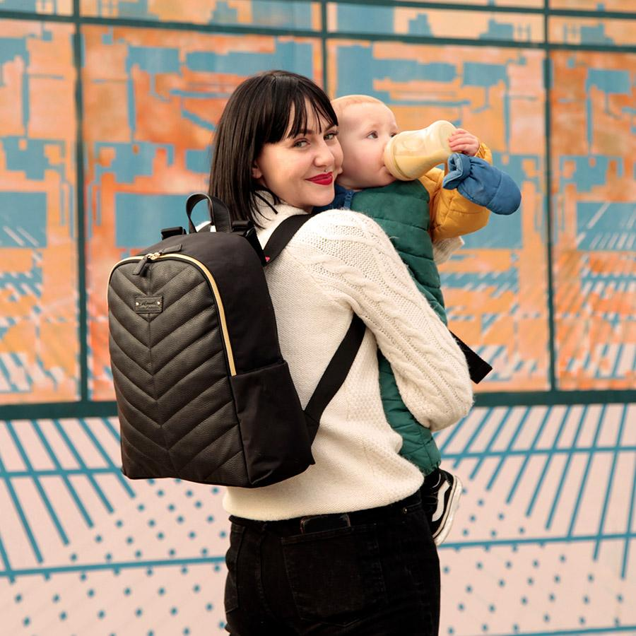 mum wearing gabby backpack black and holding baby