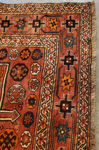 corner view of a Hand-Knotted Qashqai Rug, it has cinnamon fringe, white borders and light paprika colored main border with geometric patterns