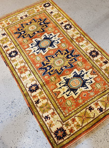 Angled view of th Turkish Wool Rug with geometric patterns, 4 medallions aternating in Gold and Black
