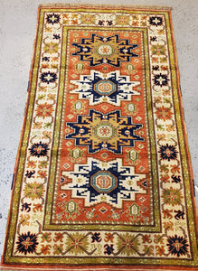 Full view of this Caucasion rug thin sage colored guards and white main border