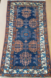 a hand knotted rug runner with 3 borders and Blue field Floral and geometric shapes