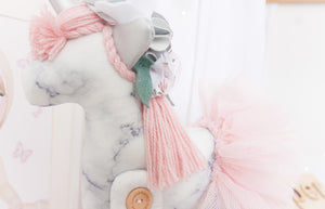 RubyBabyDesigns Keepsake Collective Heirloom Deluxe Unity the Unicorn Ballerina is a lovely soft grey and white marble digital print. Paired with a soft blush wool mane and tail, along with tulle ballerina skirt. She also has shabby flowers set within her mane and silver faux leather ears and horn. Handmade engraved wooden buttons on the legs, and filled with PET environmentally friendly fill, handmade and designed in Melbourne.