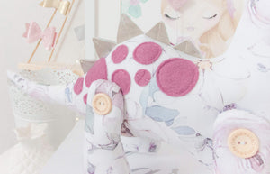 RubyBabyDesigns Keepsake Collective Heirloom Luxe Cloth Dinosaur Keepsake, created with luxurious digital printed cotton. Faux leather in a champagne colour for back spines, and wool blend plum toned felt as applique spots. Stuffed with premiun PET fill and handmade and designed in melbourne. Featuring a soft watercolour digital floral print on the body with soft pinks, maroons, plums, greens and blues on a white base. 4 engraved wooden buttons on jointed legs. Heirloom Cloth Decor keepsakes.