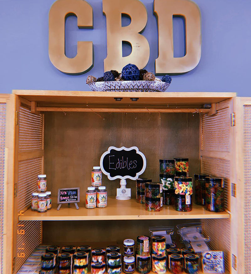 CBD gummies and edibles in a cupboard, image from CBD store of Aug on Instagram