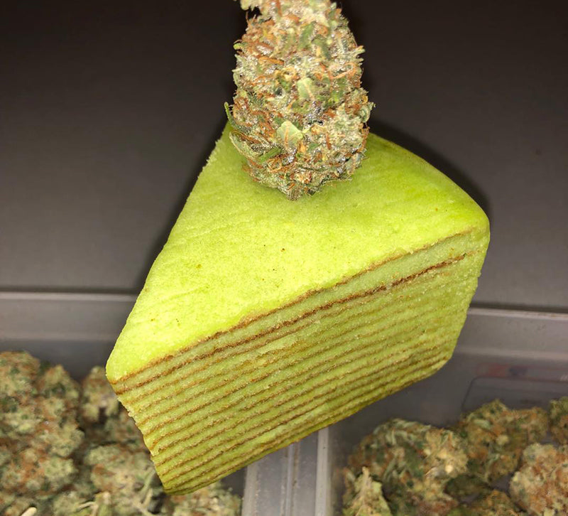 Layered cannabis cake and nugs of weed, image from Coffeshop Bellamy on Instagram
