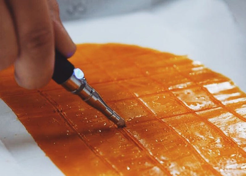 Slicing some CBD dab wax into squares, image from Grass Door.Com on Instagram