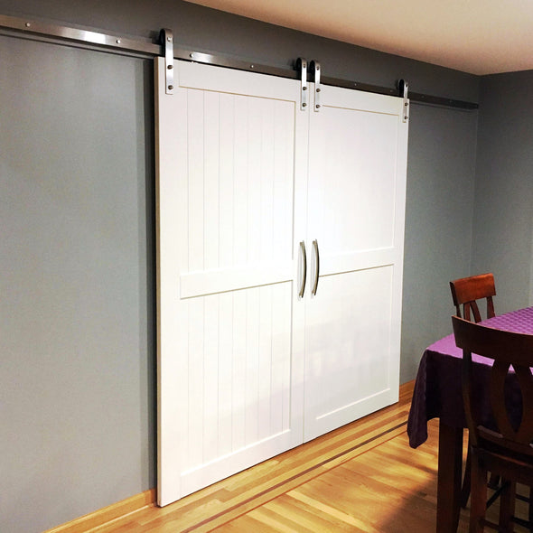 Sleekly modern Divided doors in white, with stainless steel Straight Strap soft close barn door hardware.
