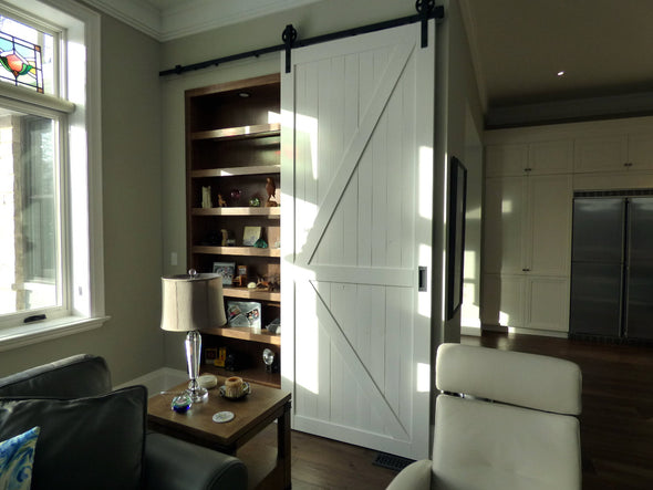 "Creamy ""K"" style doors with soft close Big Wheel hardware, covering a closet"