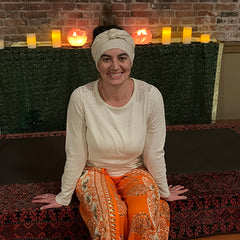 Photo of Ashley with orange pants and candles