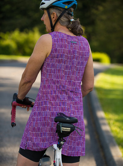 Rear view of woman biking in Dynamite Ruu-Muu pocket exercise dress, running dress, travel dress, athletic dress