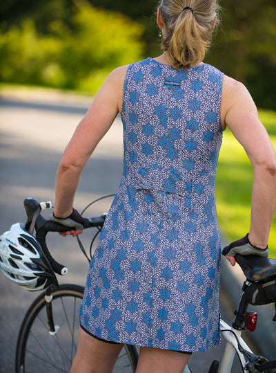 Rear view of woman standing with bicycle in Float Ruu-Muu pocket exercise dress, running dress, travel dress, athletic dress