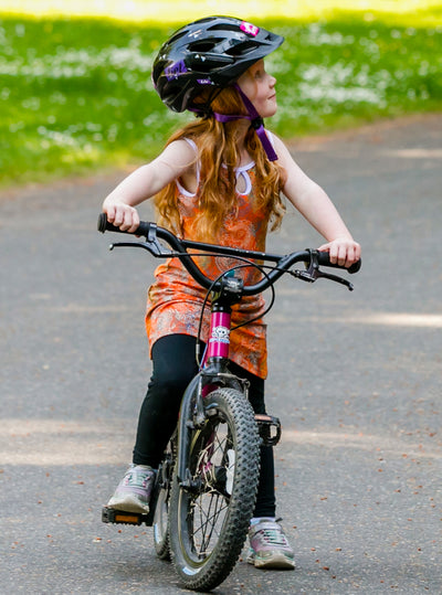 Young girl biking in Goldfish Mini-Muu play dress, kids dress, running dress, party dress.