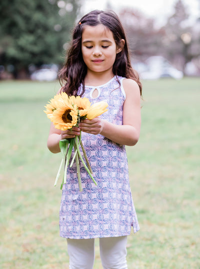 Young girl holding sunflowers in Pinklet Mini-Muu play dress, kids dress, running dress, party dress