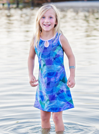 Young girl standing in Splash Mini-Muu play dress, kids dress, running dress, party dress.