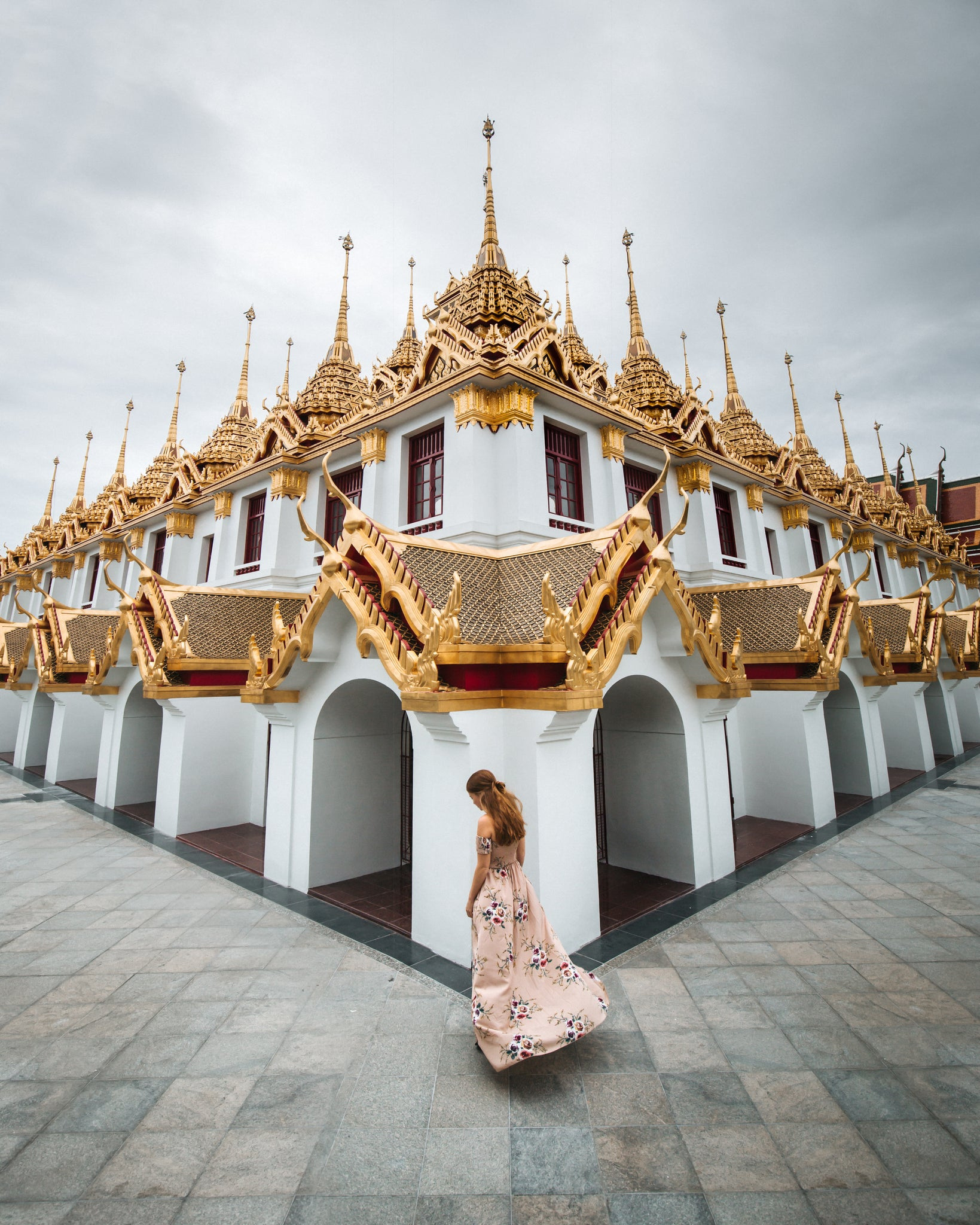 Girl walking around Loha Prasat temple, Bangkok, Thailand