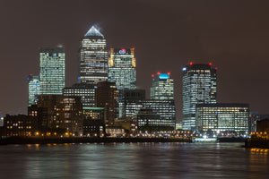 Skyline of canary wharf skyscrapers at night reflecting off water