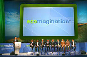 nine people sitting in row on stage with person at podium and ecomagination image projected in background