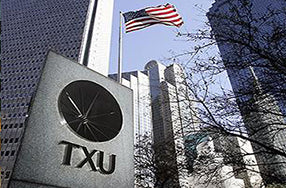TXU logo on austere sign against skyscraper building