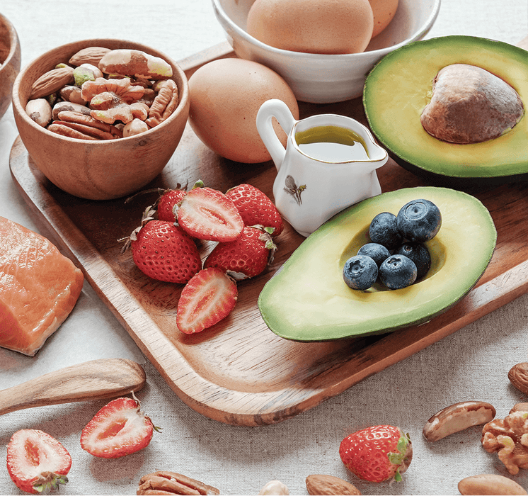 A delicious selection of keto-friendly foods including avocados, raw salmon and extra-virgin olive oil.