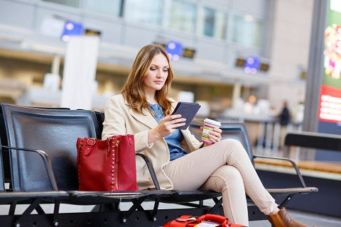 Young woman at international airport, reading her ebook and drinking coffee while waiting for her flight