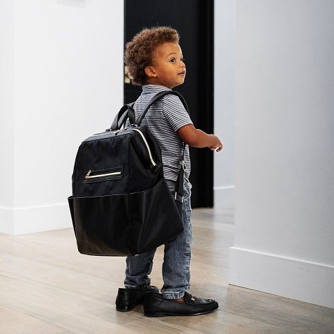 Cute afro-american toddler wearing his diaper bag on his back and funny. too big dad's shoes on his feet