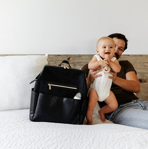 Dad holding smiling baby on the bed next to a diaper bag