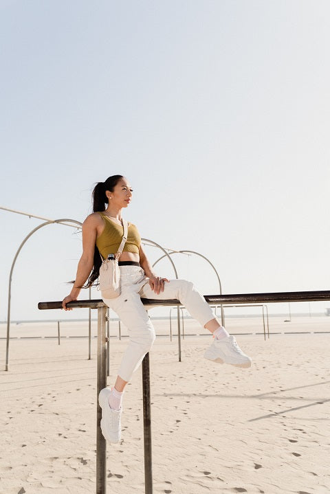 Sporting woman sitting on the beach outdor gym equipment