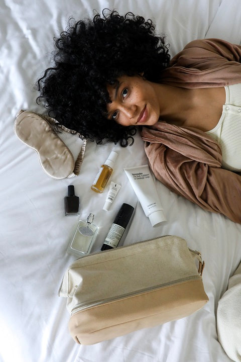 Smiling woman laying on a bed next to half packed dopp kit bag