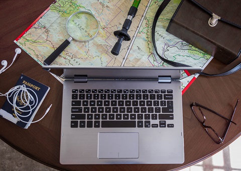 grey laptop sitting on wooden table next to glasses, passport, map, walking stick and brown messenger bag. This is for a freelance writer or author with wanderlust seeking adventure and freedom