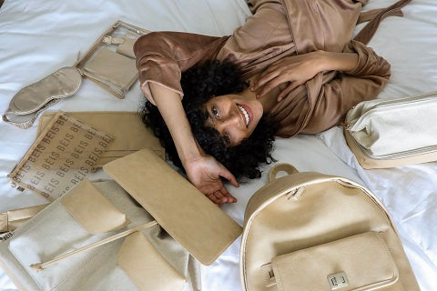 Sliling woman lying on a bed in he middle of packing
