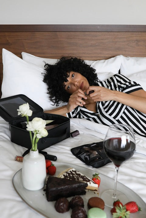 Smiling woman lying on bed, next to her is a tray with chocolates and glass of wine