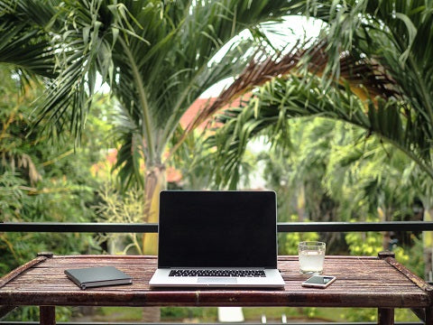 laptop of a remote digital nomad on a wooden bamboo table with notebook, mobile phone and glass in nature with a green tropical background with palm trees