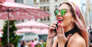 Beautiful Woman laughing and talking on phone; Wearing Retro Sunglasses Cat Eye in Mirrored Pink Lens & Leopard Rose Gold Frame