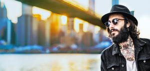 A man in Black Jacket and black, with Brooklyn Bridge in Background, Wearing Club Mater Sunglasses