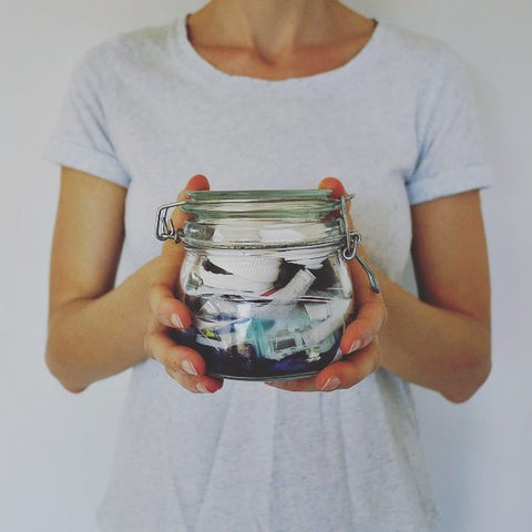a girl wearing white tshirt behind white plain background holding a jar with garbages in it