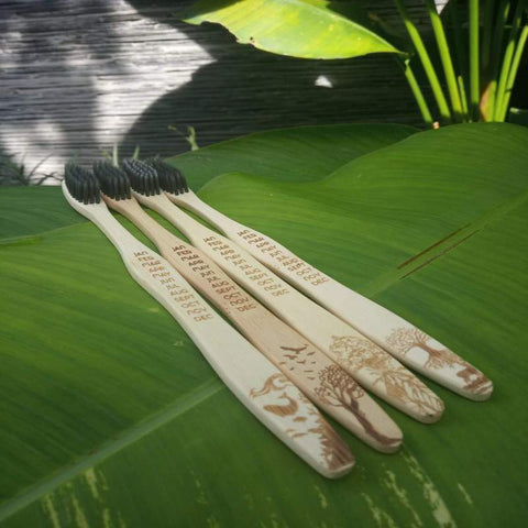 four bamboo toothbrush with black bristles on a green leaf