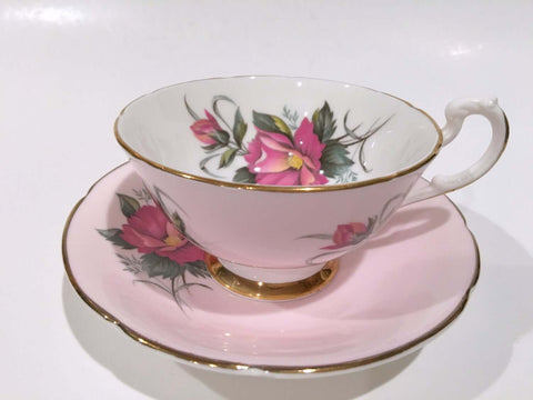 pink tea cup on a pink bowl with white background