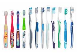 variety sizes of plastic toothbrush behind white plain background