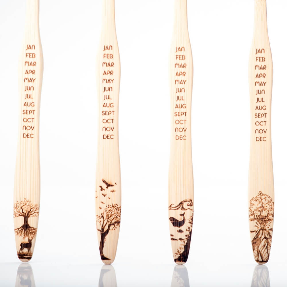 four bamboo toothbrushes next to each other with each a different design of the four elements
