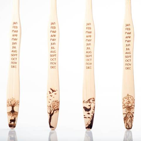 Image of four bamboo toothbrushes next to eachother with each a different design of the four elements