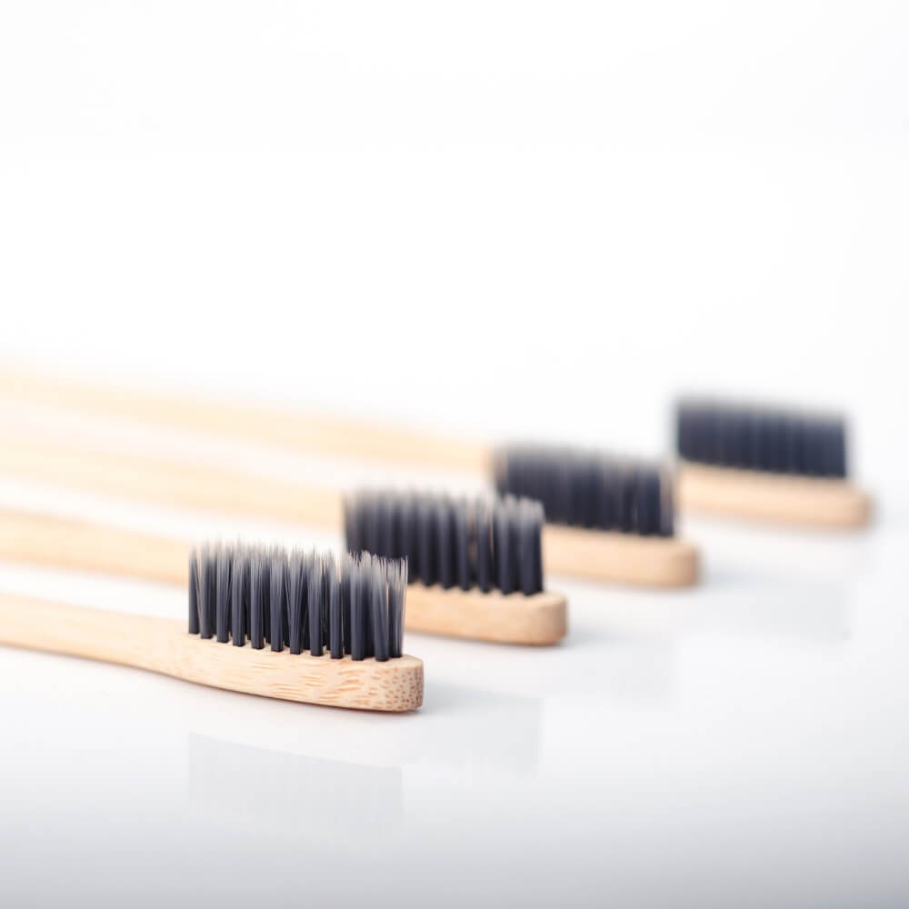 four bamboo toothbrushes laying next to eachother with a white background