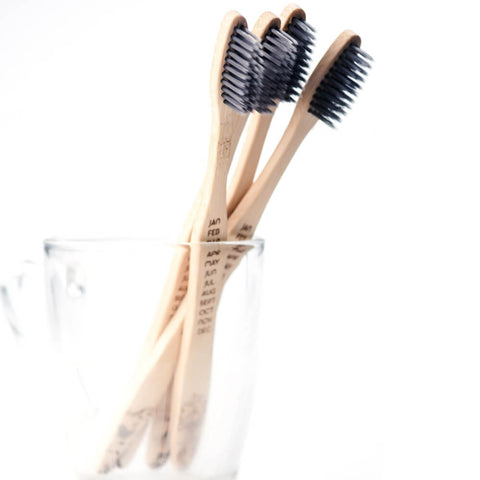 four bamboo toothbrushes standing upright in a glass and a white background