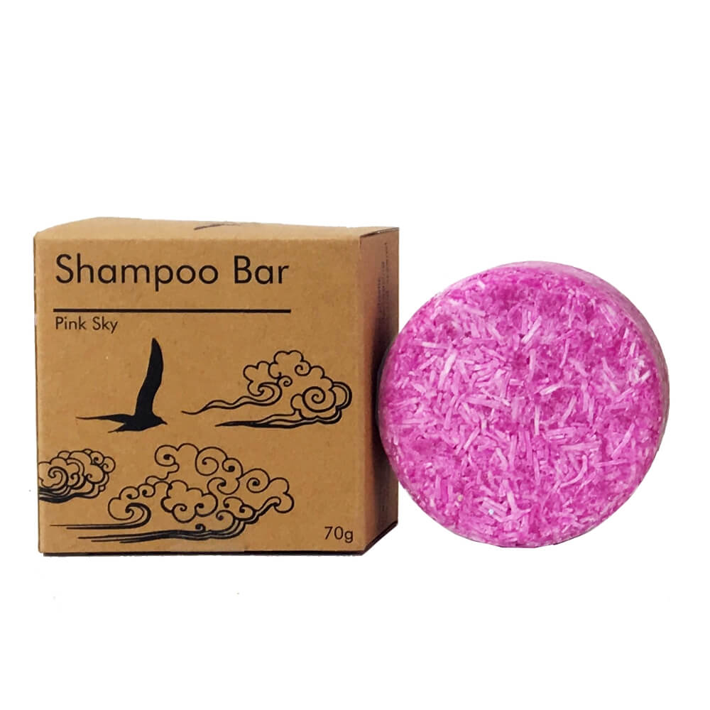 shampoo bars in three different colors and kraft packaging printed in black ink pink sky with flying bird and clouds