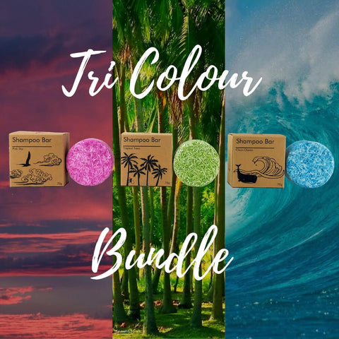 Image of shampoo bars in three different colors and kraft packaging printed in black ink pink sky tropical trees blue ocean