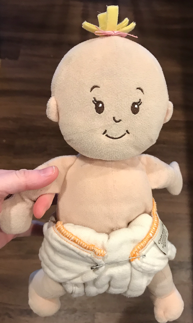 The angel fold using a prefold cotton diaper, as practiced on my daughter's doll.