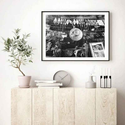Framed black and white wall art print of a Bangkok Floating Market vendor on her boat grilling seafood hung above a console table.